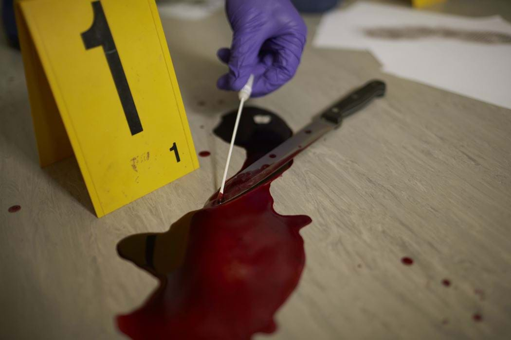 A hand can be seen using a cotton swab to take a sample from a blood stained knife
