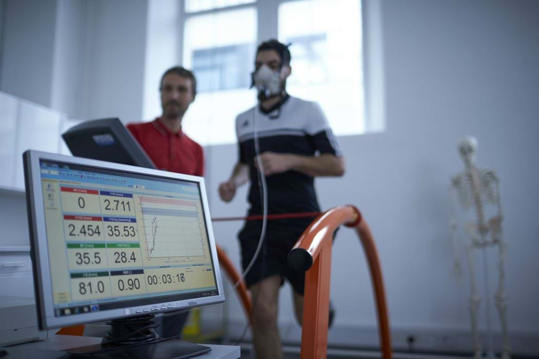 Male wearing breathing apparatus whilst running on a running machine - another male is standing beside him watching