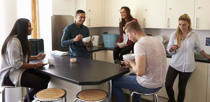 Group of five young adults huddled around a breakfast bar in a kitchen, three girls and two guys, three of the young adults are looking at their smartphones.
