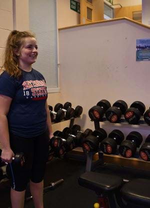 Gym environment - female using small dumbbells