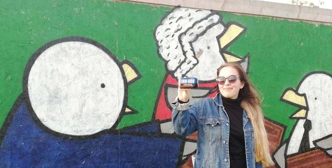 A photo of Barbara Szpilka holding a can of Irn Bru in front of seagull grafitti