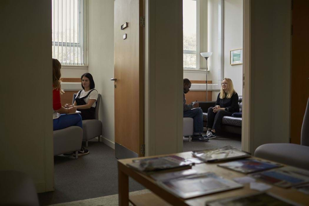 Two rooms - room 1 shows a female counselling another female. room 2 shows a male counselling a female