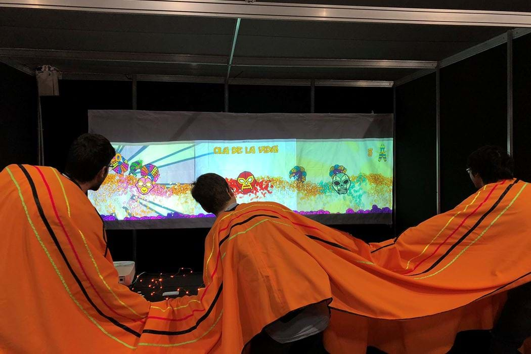 Three students in a three-person poncho playing an interactive game