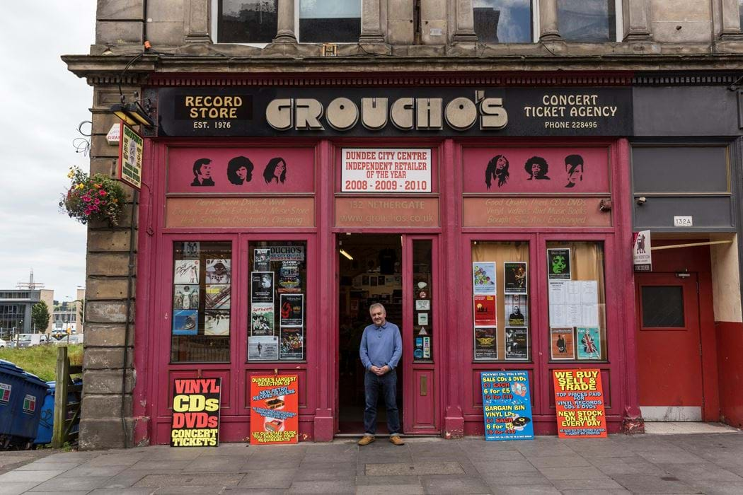Male standing outside Groucho's shop