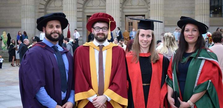 Four post graduate students wearing graduation gowns