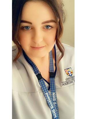 A selfie of Caroline Ford, in a nurses uniform with an Abertay University logo on her right. Caroline is also wearing an NHS Scotland lanyard arount their neck.