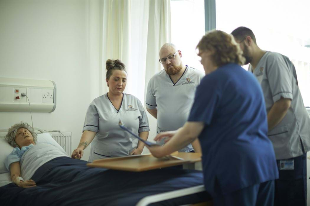 Hospital environment - patient lying in bed and 4 Nursing staff standing around the bed
