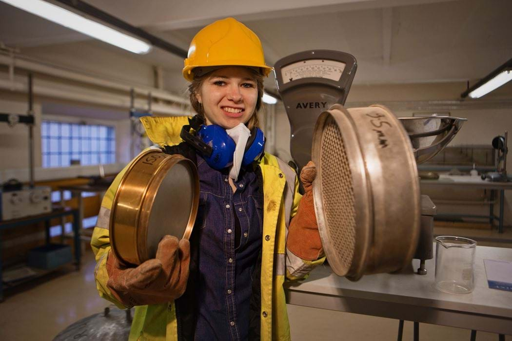 Female engineering student holding 2 circular objects