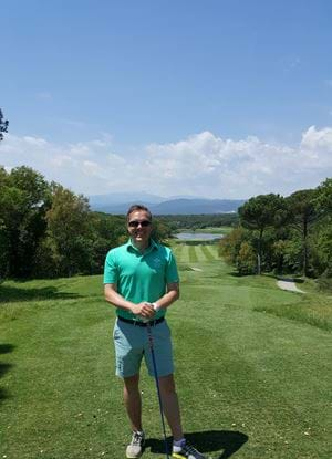 Fraser on a golf course with mountains in the background and a golf club in his hands