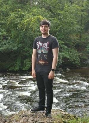 A photo of Kieran McGurk standing by a river