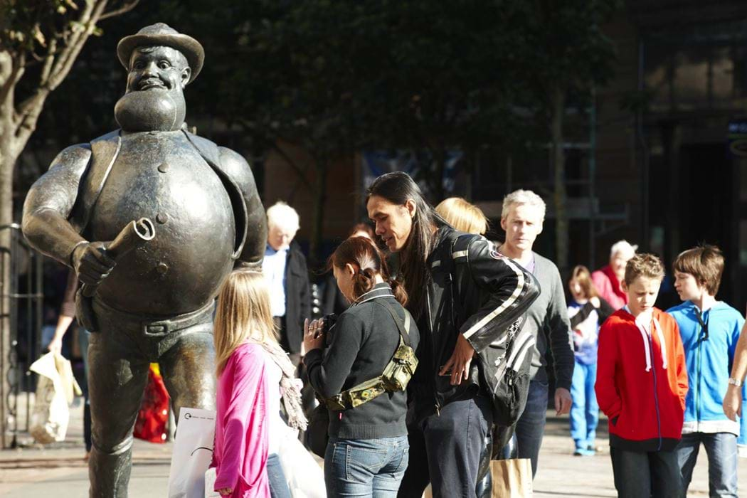 Group of people standing beside the Desperate Dan statue in Dundee City Centre