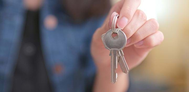 A photo of a hand holding a pair of keys. The background of the photo is blurred to emphasise the keys.