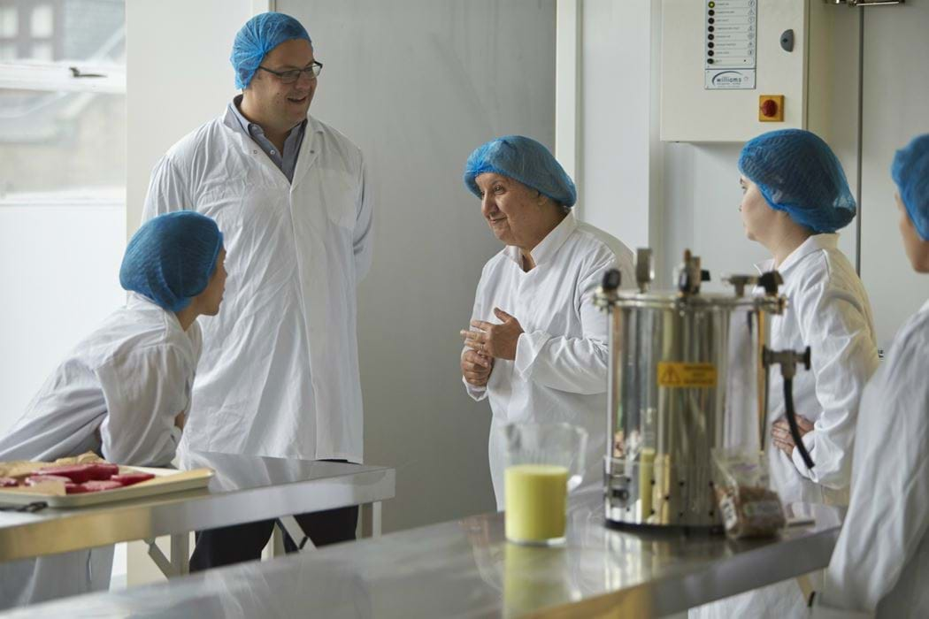 Group of people standing chatting in a food laboratory