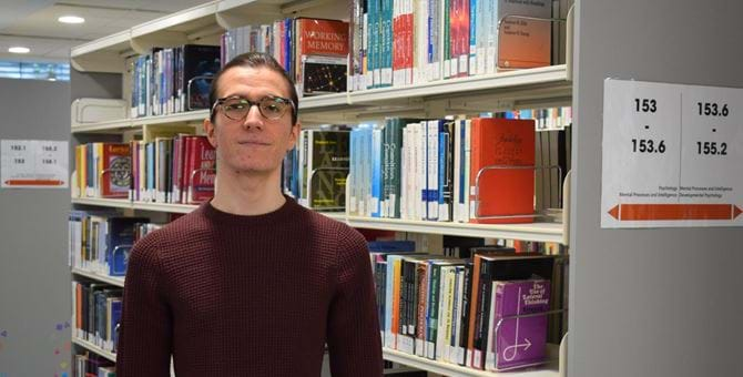 A photo of Nikolay Panayotov in Abertay University library, in front of bookshelves