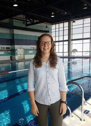 A picture of Alison Chapman standing beside a swimming pool.