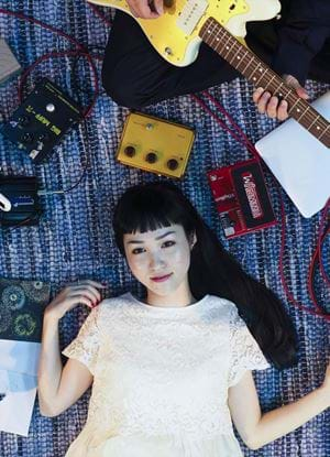 Music star  Marico lying down with instruments placed around her