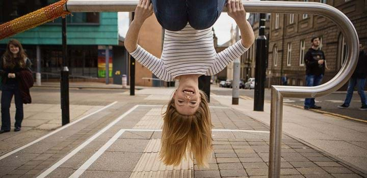 Female hanging upside down on hand railing