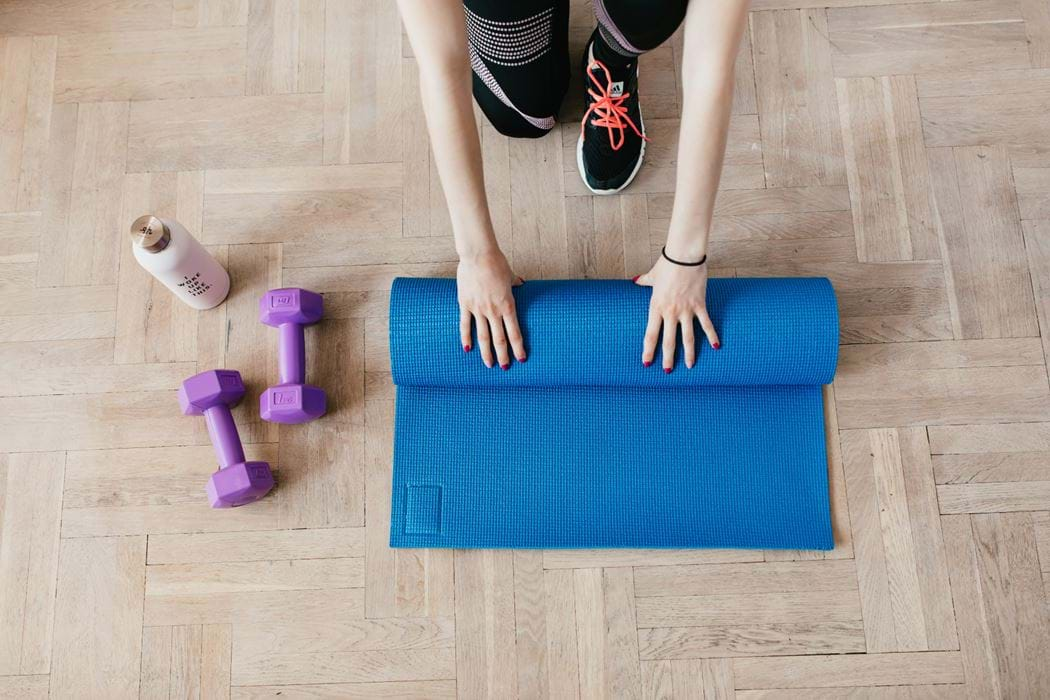 A persons hands are rolling up a yoga mat. there are also some free weights in the shot.